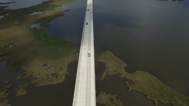 Reveal down causeway endless bridge epic long - Drone Aerial 4K Lake Pontchartrain CausewayGrand Isle Louisiana coast Mississippi river bridge and barge everglades, gulf delta, with wildlife 4K Transportation