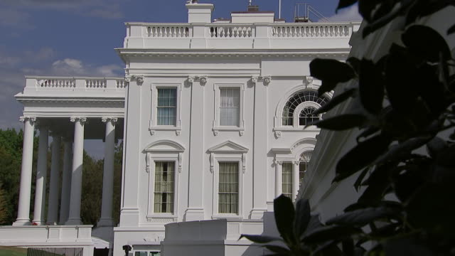 reveal from bushes of establishing shot of the white house in washington, d.c. - united states and (politics or government)点の映像素材/bロール