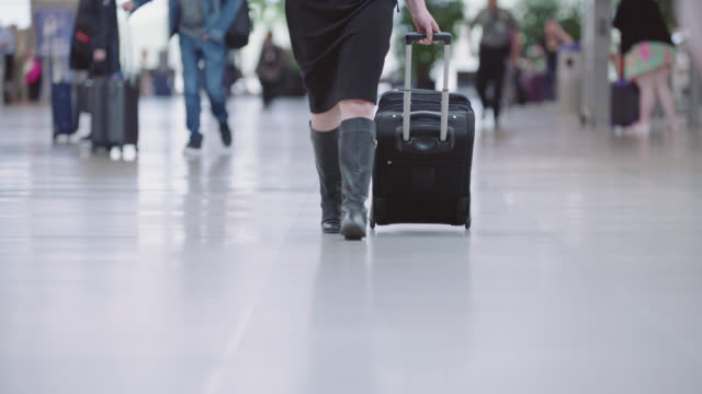 reveal of confident young businesswoman rolling suitcase through lively airport terminal. - one chance stock videos & royalty-free footage