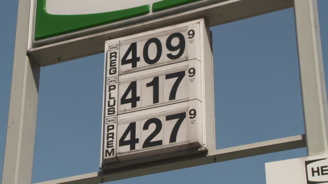 stockvideo's en b-roll-footage met reveal of high gas prices on a gas pump in new york juxtaposed with a big gas same low price cash or credit sign - benzineprijzen