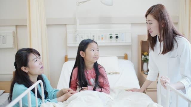 vídeos de stock, filmes e b-roll de revele da menina na cama no hospital com matriz e enfermeira - enfermeira pediátrica
