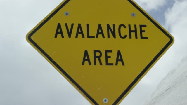 "reveal shot of an ""avalanche area"" caution road sign in the rocky mountains of colorado under an overcast sky in winter - warning sign stock videos & royalty-free footage"