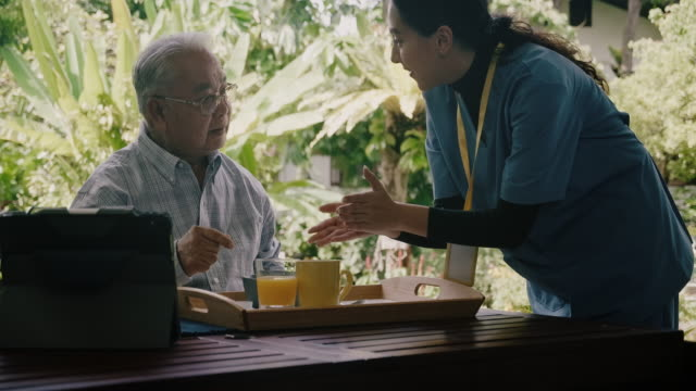 reveal shot of nurse bringing breakfast to senior adult. - 70 79 years stock videos & royalty-free footage