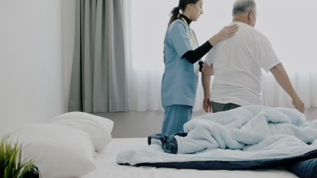 reveal shot of nurse helping senior get out of bed. - 70 79 years stock videos & royalty-free footage