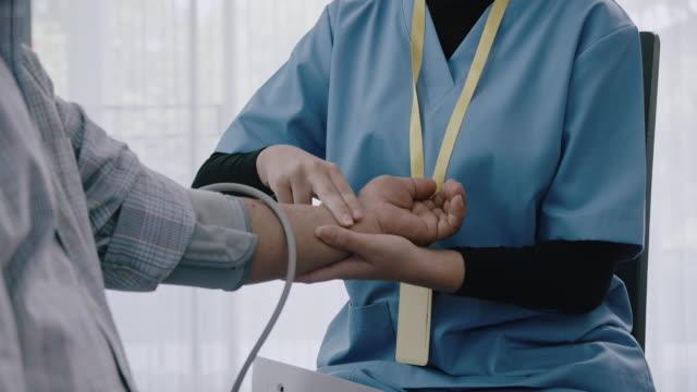 reveal shot of nurse taking blood pressure of senior man. - 70 79 years stock videos & royalty-free footage