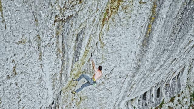 vídeos de stock, filmes e b-roll de aérea, revelando um alpinista masculino escalando um penhasco íngreme - gancho de alpinismo