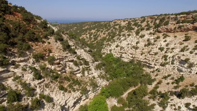 stockvideo's en b-roll-footage met revealing aerial / drone shot of a valley in cyprus revealing the coast line - valley