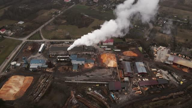 revealing shot of operating log sawmill factory with large chimney emitting smoke aerial - log stock videos & royalty-free footage
