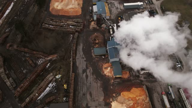 revealing top down shot of operating log sawmill factory with large chimney emitting smoke aerial - log stock videos & royalty-free footage