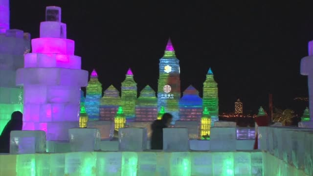 revelers brave temperatures well below freezing to see ice sculptures and slide down chutes at one of the world's biggest ice and snow festivals - gefrorenes wasser stock-videos und b-roll-filmmaterial