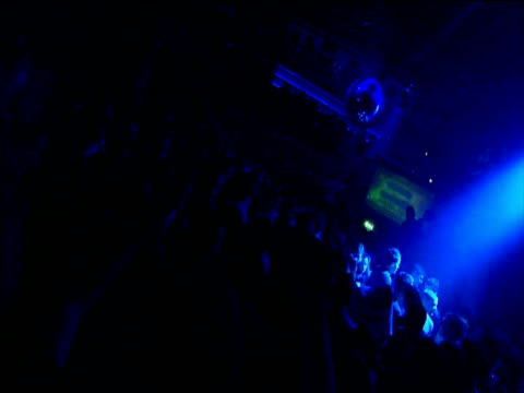 Revelers raising hands in the air in club flooded with blue strobe lights