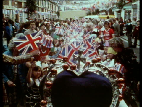 revelers wave flags to camera while surrounding children's party during silver jubilee celebrations 7 jun 77 - street party stock videos and b-roll footage