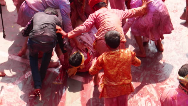 Revellers celebrating Holi, festival of colours, by covering each other with water and colour and dragging across the floor