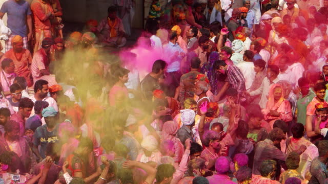 revellers enjoying themselves and throwing dry colour powder in the air during holi celebrations in india - spiritualität stock-videos und b-roll-filmmaterial