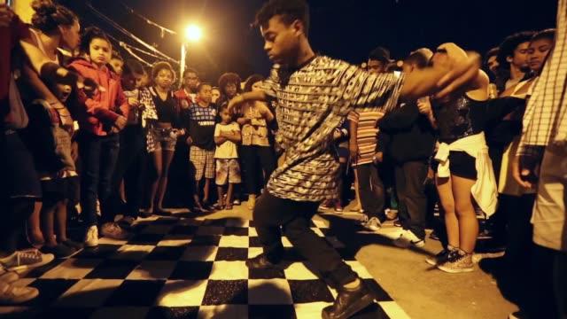 vidéos et rushes de revellers gather and dance at the 'black santa' party held in the prazeres favela, or community, on september 7, 2014 in rio de janeiro, brazil. - dancing