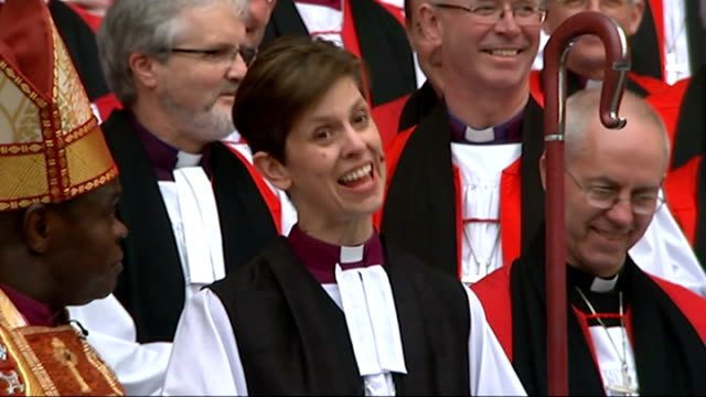 reverend libby lane consecrated as first female church of england bishop; ext lane standing in front of group of cheering bishops sot lane smiling... - anglican stock videos & royalty-free footage