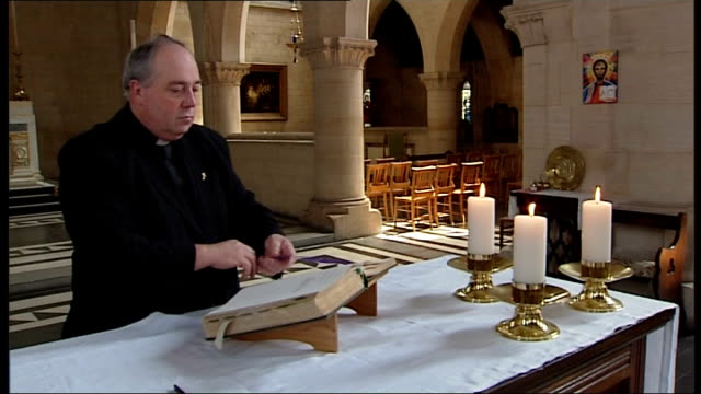 Reverend Lucy Winkett conducts St Paul's service Man lighting candles and laying bible on altar ahead of service