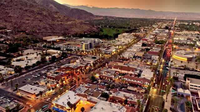 reverse aerial over downtown palm springs at dusk looking north to san bernardino mountains and wind farm in far distance - palm springs california stock videos & royalty-free footage