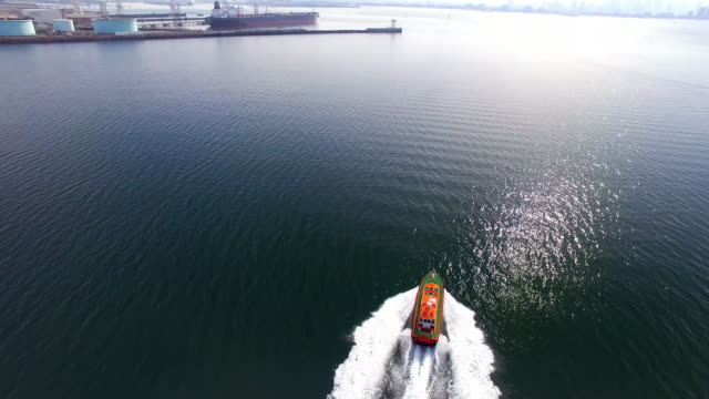 a reverse aerial shot of a pilot boat speeding across a smooth ocean to greet its vessel to enter the shipping docklands. - david ewing stock videos & royalty-free footage