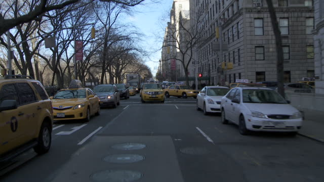 Reverse POV driving down 5th Avenue in clow moving traffic.  Lots of cabs are in the frame.