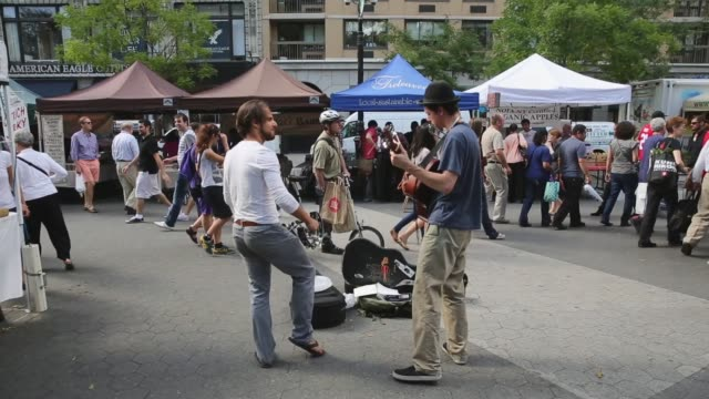 reverse long shot street musicians performing at greenmarket shoppers visit the greenmarket at union square park new york city's largest farmers... - union square new york city stock videos & royalty-free footage