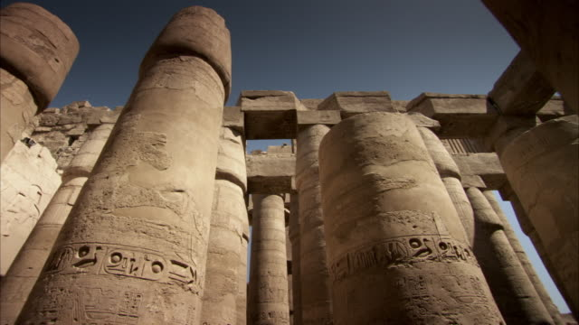 Reverse tracking shot between the stone pillars of an ancient Egyptian temple.