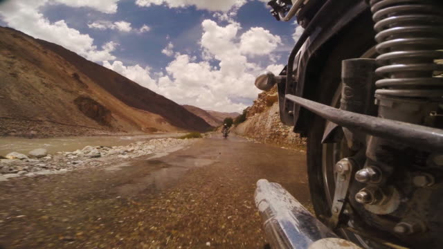 reverse view of two bikers driving royal enfields through mountain landscape in india, splashing puddles as they drive - royal blue stock videos & royalty-free footage