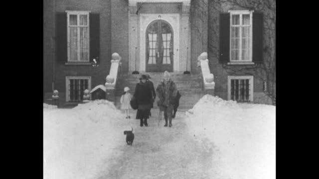 reversed image of title page in german and dutch / shot of door to house, snow on ground; wilhelm, his wife hermine and hermine's children come out... - 追放点の映像素材/bロール