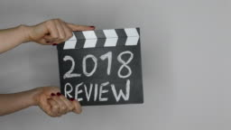 2018 review. Hands holding movie clapper