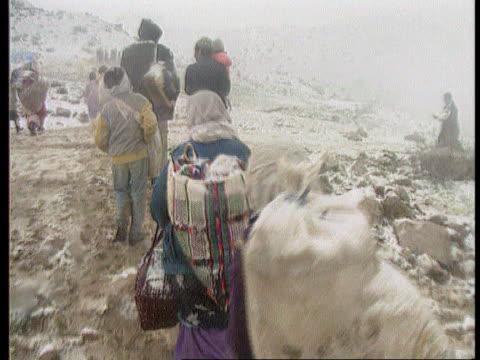 review of headlines; iraqi / turkish border day / snow on ground seq kurdish refugees along up hill tx 8.4.91 - クルド人点の映像素材/bロール