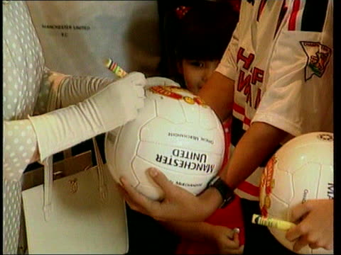nicholas lib queen elizabeth ii with sir bobby charlton and supporters of manchester united fc queen autographing football held by boy cs signature... - autographing stock videos and b-roll footage