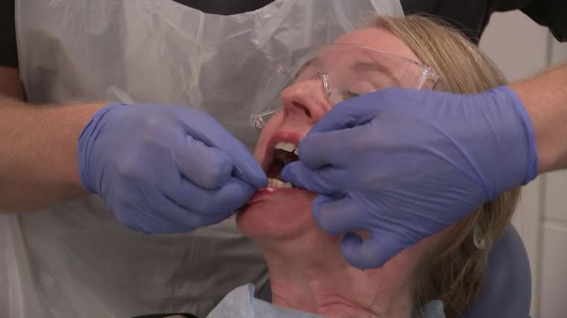 nhs reviews evidence that flossing is beneficial scotland glasgow int low angle shot dentist working seen through false teeth various shots dentists... - dentures stock videos and b-roll footage