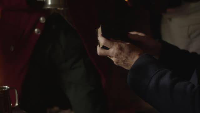 revolutionary reenactment of man signing document in tavern - bricco video stock e b–roll