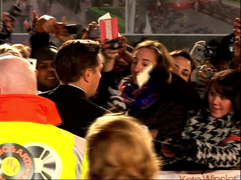 'revolutionary road' premieres in london's leicester square; dicaprio signing autographs for fans as hugs winslet then both away / back views of... - リズ・マクラーノン点の映像素材/bロール