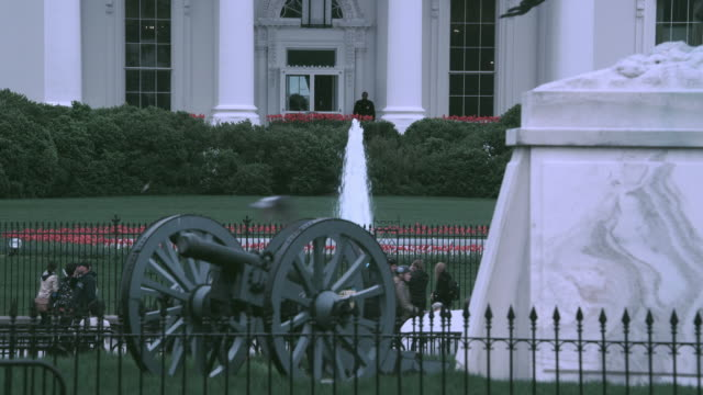 HA Revolutionary War cannon, fountain, and pedestrians in Lafayette Park, North Portico of the White House beyond / Washington, D.C., United States
