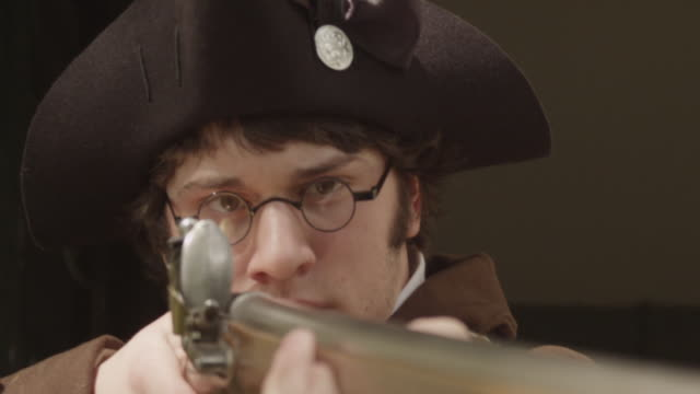 vídeos y material grabado en eventos de stock de revolutionary war soldier in tricorn hat aiming musket - tricornio