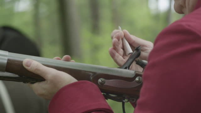 revolutionary war soldier loading powder into musket - gewehr stock-videos und b-roll-filmmaterial