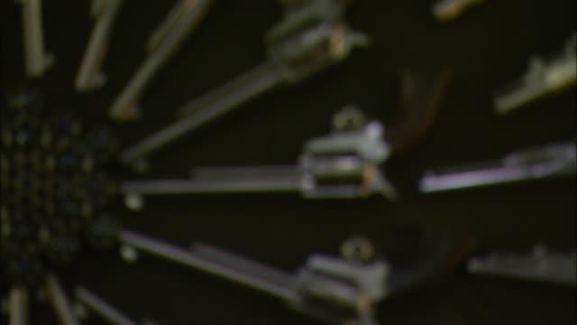 revolvers arranged in a circular pattern point to gun cylinders on a handgun display. - gun barrel stock videos & royalty-free footage