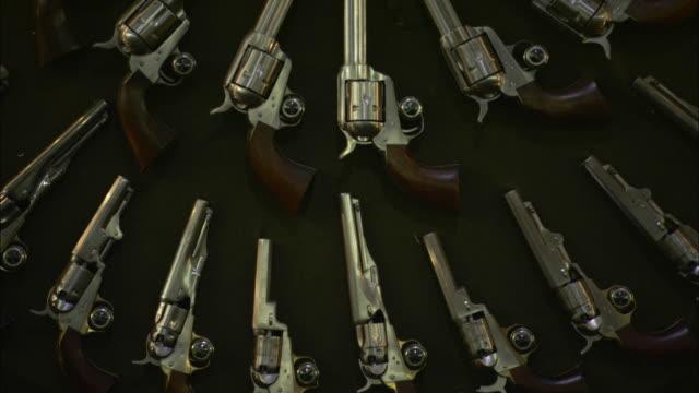 revolvers encircle gun cylinders on an artfully arranged gun display. - gun barrel stock videos & royalty-free footage
