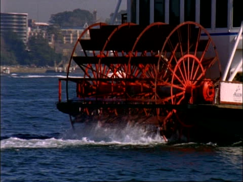 cu revolving paddles of paddle boat passing in front of sydney opera house, sydney , australia - paddle boat stock videos & royalty-free footage