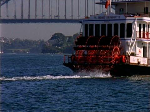 cu revolving paddles of paddle boat zooms out wa harbour bridge, sydney , australia - paddle boat stock videos & royalty-free footage