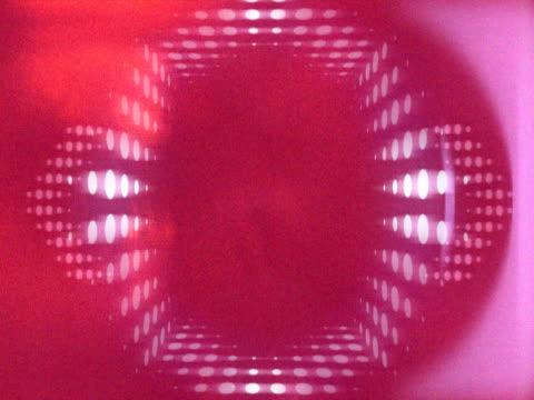 vídeos de stock e filmes b-roll de revolving red kaleidoscopic pattern and bright light - multimédia