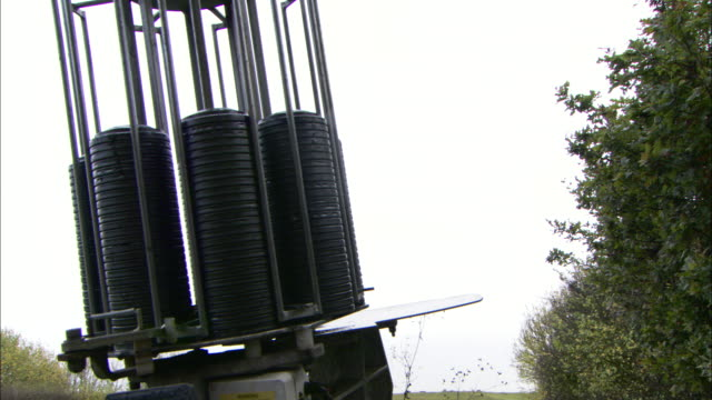 a revolving target thrower projects clay pigeons into an overcast sky. - クレー射撃点の映像素材/bロール
