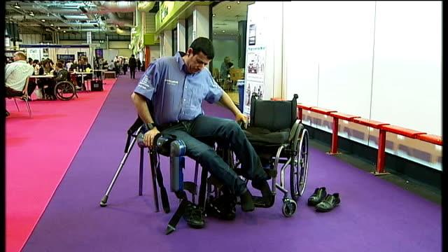 rewalk robot exoskeleton helps paraplegics walk england birmingham radi kaiof out of wheelchair and walking with aid of rewalk exoskeleton attached... - exoskeleton stock videos & royalty-free footage
