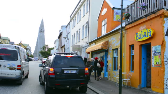 reykjavik iceland downtown colorful restaurant and shops on street near the hallgrimskirkja church in background - bicycle parking station stock videos and b-roll footage