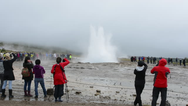 Reykjavik Iceland tourists waiting for erruption of the famous Stokkur geyser on a foggy day