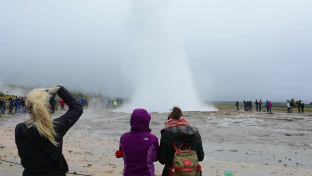 reykjavik iceland tourists waiting for erruption of the famous stokkur geyser on a foggy day - reykjavik stock videos and b-roll footage