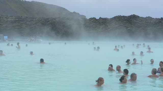 reykjavik iceland world famous blue lagoon of hot geothermal mineral thermal springs with tourists relaxing in the warm water in grindavik - hot spring stock videos & royalty-free footage