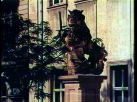 1953 montage pan rhine river in heidelberg / cu lion statue / ws td yard at heidelberg university / ms students sitting outdoors / heidelberg, germany / audio - ハイデルベルク点の映像素材/bロール
