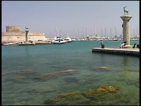 stockvideo's en b-roll-footage met rhodes, greece: harbor entrance with brass deers and fort walls - rodos dodecanese eilanden